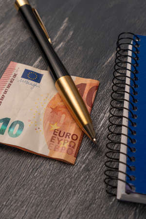 Pen with notebook and euro banknote. Business. On a dark wooden table