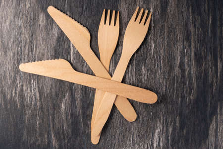 Wooden knives and forks on gray art wood background