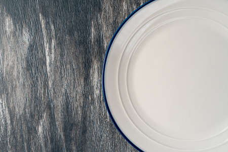 White plate with blue border on a beautiful gray wooden background. Empty kitchen utensils on art surface. Copy space