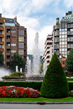 Oviedo, Spain, Asturias - August 2020: Beautiful city landscape with fountain and colorful lawn with red and white flowers in America Square, Oviedo, Spain