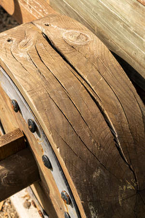 Old cracked wooden wheel of an ancient cannon. With iron mounts. Close-up. Historical Landmark Detail Standard-Bild