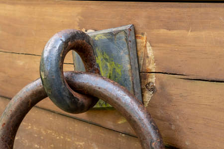 Ancient rusty ring on a cracked weathered wooden board close up Standard-Bild