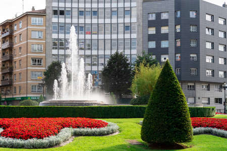 Oviedo, Spain, Asturias - August 2020: Square with a fountain and beautiful flowers and vegetation against the backdrop of buildings and the sky in America Square. City landscape. Oviedo. Spain. Asturias