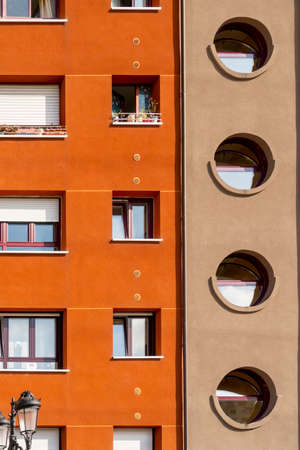 Oviedo, Spain, Asturias - August 2020: Bright facade of a residential building. Geometric shapes. Rectangular and round windows. Abstract concept