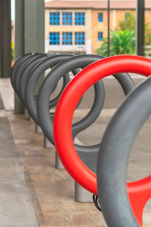 Bicycle parking area. Bright red ring in a row of grays. The concept of individuality and uniqueness