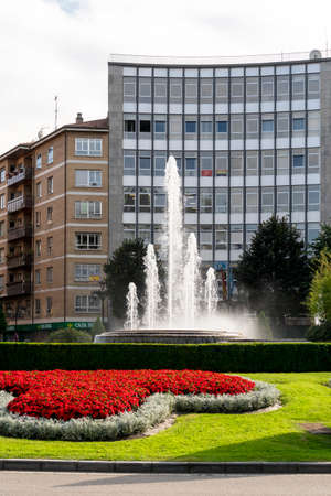 Oviedo, Spain, Asturias - August 2020: Square with a fountain and beautiful flowers and vegetation against the backdrop of buildings and the sky. City landscape. Oviedo. Spain. Asturias