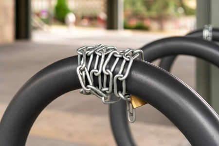 Chain lock for bike safety in the bike parking with gray iron rings. Lifestyle and safety concept