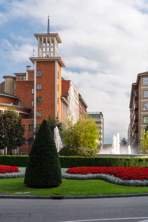 Oviedo, Spain, Asturias - August 2020: Fountain in the city square with green lawn and bright flowers on the background of buildings in America Square Editorial