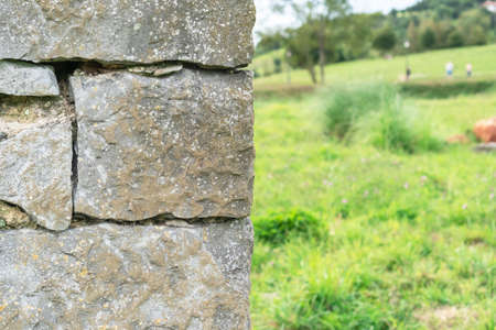 Corner of a stone wall made of rough masonry. Against the backdrop of a wooded hill with green grass and sky. Soft selective focus. Фото со стока