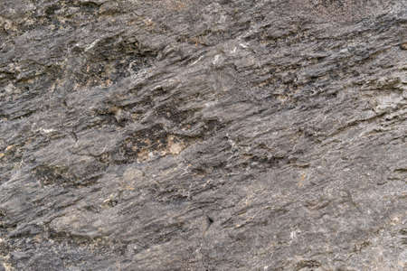 Grungy cracked stone texture from natural rock retro style. Weathered ancient wall background. Concept of aged building natural material