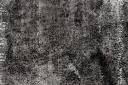 Black texture of old roofing material. Weathered mottled shabby building material with cracks. Dark abstract background