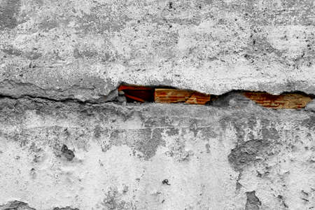 cracked concrete wall with a large crack and red bricks underneath. Destruction and ruin concept Фото со стока - 156098902