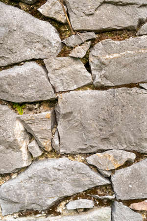 Background of stone wall close up. Piled up chaotically Фото со стока - 156098907