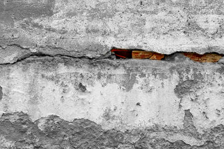 Old shabby cracked cement wall covering brickwork with red bricks. Abstract background with color contrast Фото со стока