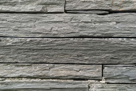 Black slate block wall texture. Background close up