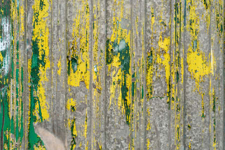 Old corrugated iron fence with peeling green and yellow paint. Abstract texture Фото со стока - 156099004