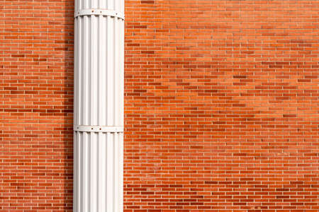 Red brick wall with white decorative column. Copspace Фото со стока
