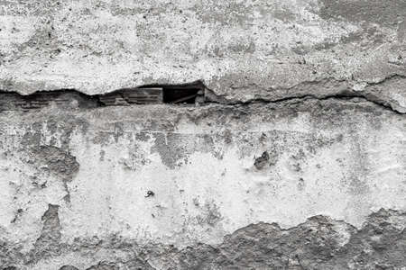 Grungy shabby concrete wall with large cracks. Gray textured abstract background