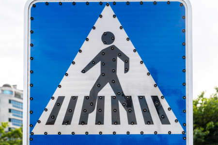 Pedestrian crossing road sign with off LED backlight close-up against the background of the sky, city and trees.
