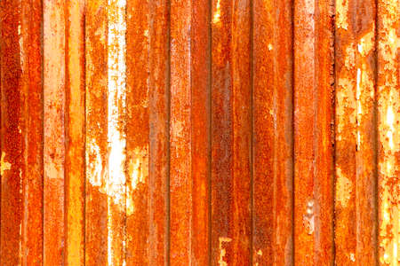 Old rusty door of an abandoned fence made of corroded galvanized material. Bright abstract texture with high resolution Фото со стока