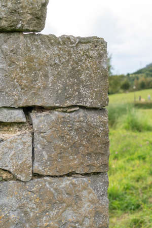 Corner of a stone wall made of rough masonry. Against the backdrop of a wooded hill with green grass and sky. Soft selective focus. Фото со стока - 156099198