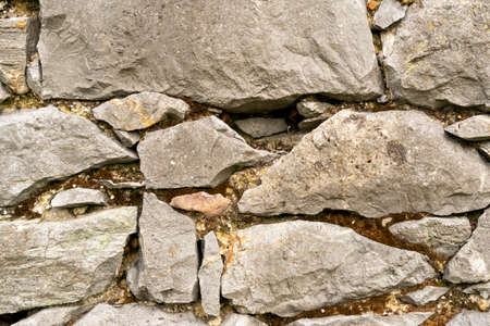 Background of stone wall close up. Piled up chaotically Фото со стока