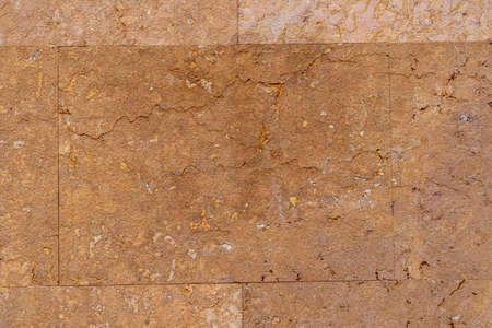 Old weathered brown wall tile with cracks in high resolution close up