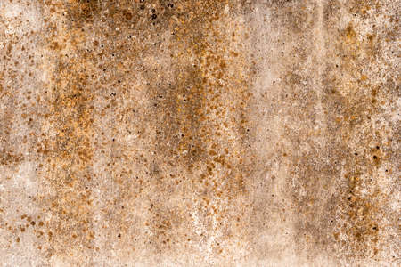 Vintage grunge background with shades of rust on the old concrete wall, cracks and textures of golden brown stains Фото со стока