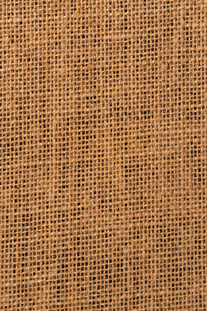 Burlap background close-up on a black background. Dark base. Braided sackcloth material. Vertical view Фото со стока - 156354880