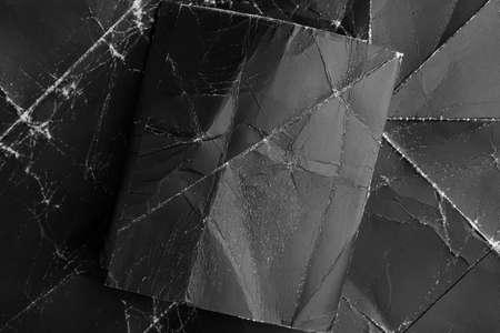 Black crumpled square Poster on grunge wrinkled cardboard close up. Grunge abstract mock up