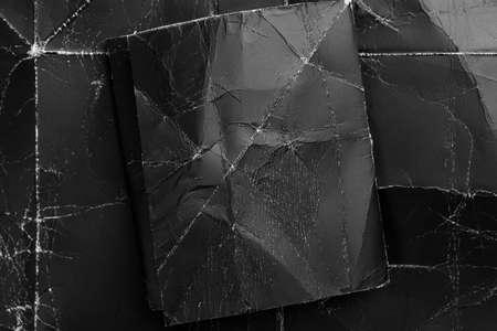 Black crumpled paper on a black shabby grunge background. Dark paper mock up for design. Folded sheet on a dramatic background. Vintage mock up