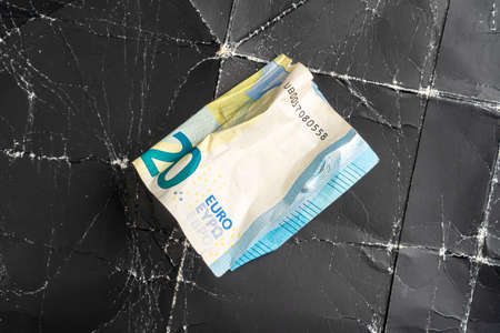 Crumpled twenty euro banknote on crumpled black wrinkled paper close up Фото со стока - 156354890