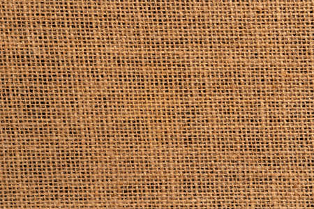 Burlap background close-up on a black background. Dark base. Braided sackcloth material Фото со стока