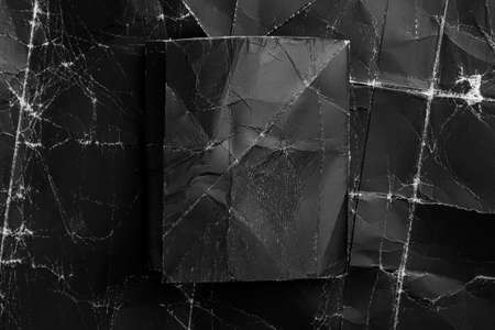 Piece of folded black crumpled paper on an old, wrinkled, shabby packing cardboard. abstract background with copy space for labels and titles. Black on black Фото со стока
