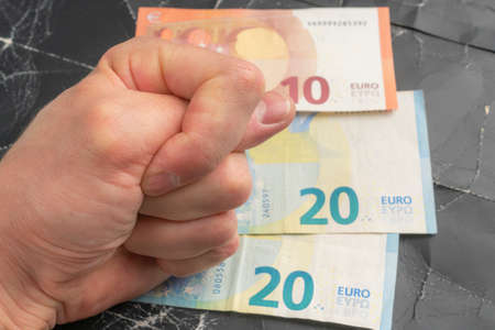 Euro banknotes on a black crumpled background. The hand shows a gesture of refusal and protest. Financial crisis and economic sanctions concept