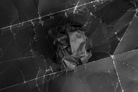On black wrinkled old paper, a crumpled black ball. close-up. Black on black