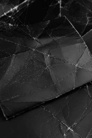 Black wrinkled paper crumpled piece on an old shabby black packaging cardboard close-up. Vertical view. Black on black Фото со стока