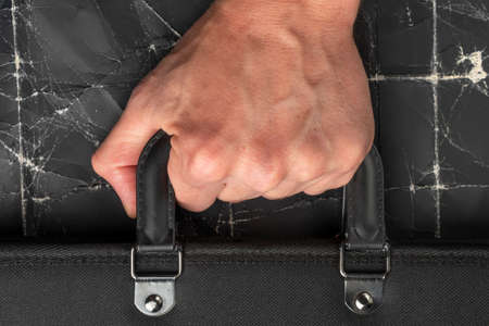 Close-up of the hand of a bankrupt business man or fired worker holding the handle of a suitcase against a grunge background of crumpled black paper. Unemployment and financial crisis concept. Stock fotó