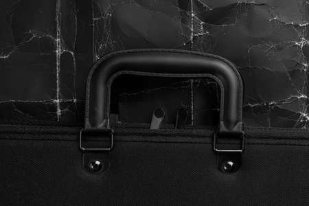Black business briefcase on wrinkled black packing cardboard. Abstract vintage unemployment crisis concept. Abandoned accessory in synthetic textured fabric with leather handles. Copy space. Close-up