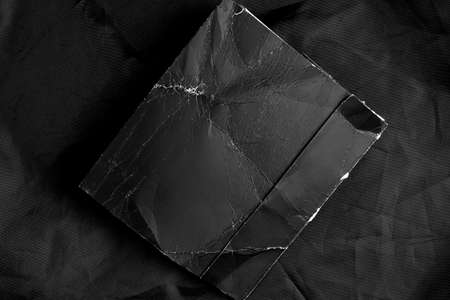 Black grunge crumpled paper on black wrinkled synthetic material. Close-up. Vintage mock up. Copy space.