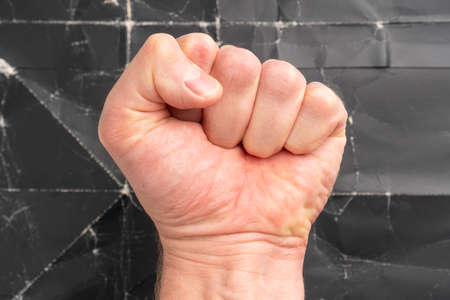 Male clenched fist on black grunge background. Freedom protest and struggle concept