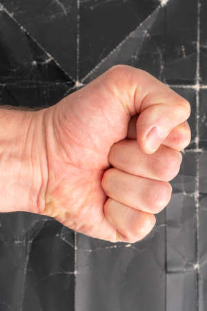 Fist strikes on grunge background of old crumpled black paper close up Stock fotó