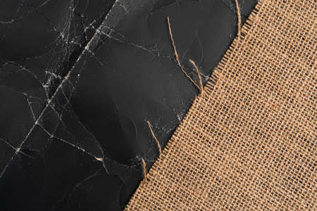 Burlap on black crumpled paper with wrinkles and folds. Abstract background with sackcloth on grunge backdrop Stock fotó