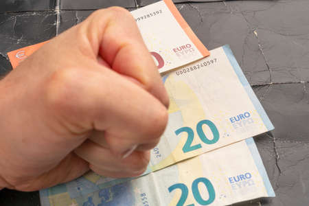 Young man's fist on a stack of euro banknotes on a black shabby crumpled paper background. The idea of the eurozone crisis and the European financial crisis 版權商用圖片