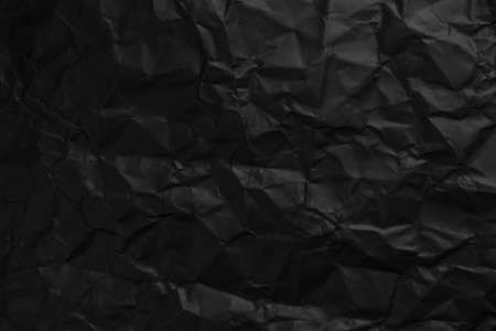 Black background texture of crumpled paper close-up. Faded texture folds