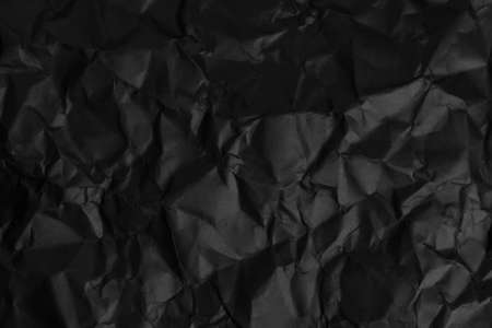 Textured abstract background from black crumpled paper. Dark worn abstraction