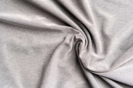 Synthetic wrinkled sporty gray fabric with wrinkle pattern. Polyester textured crumpled background.
