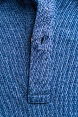 Closure of a blue polo shirt with a button close-up. Fashion background. Copy space
