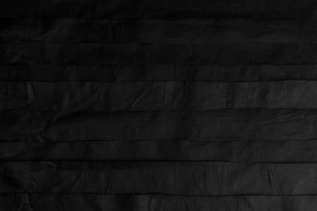 Black crumpled synthetic stripes. Wrinkled horizontal layers. Abstract dark background