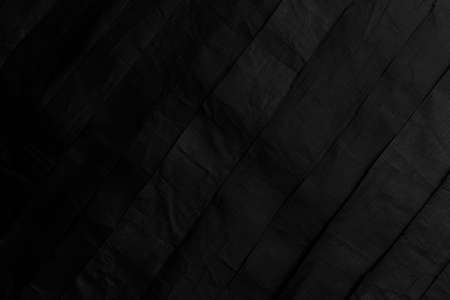 Closeup of black fabric synthetic crumpled stripes. Abstract background Фото со стока